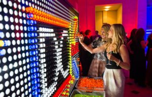 Two women playing litebrite at a party